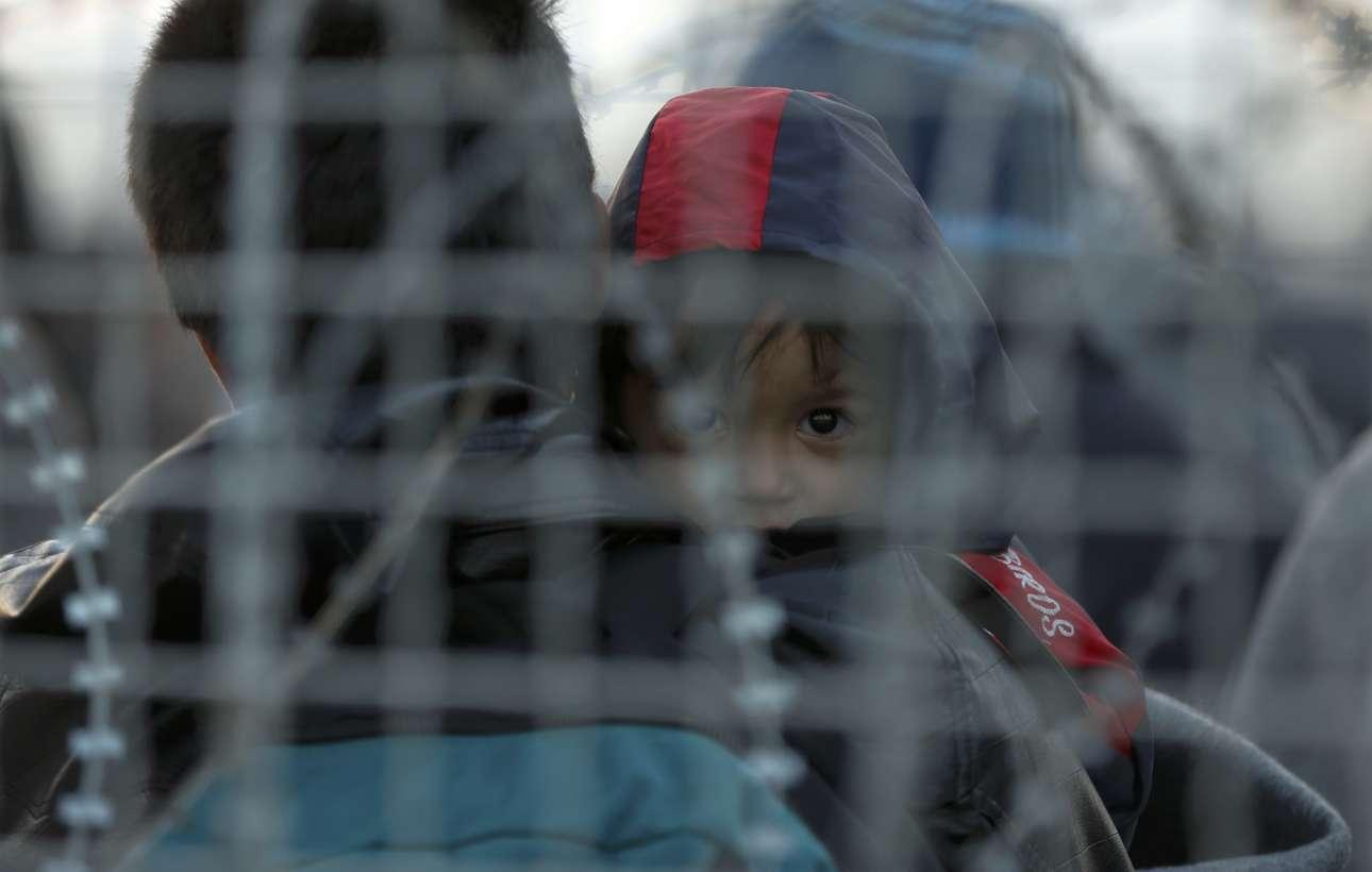 Ενα μικρό αγόρι κοιτάει μέσα από έναν φράχτη τον φωτογραφικό φακό