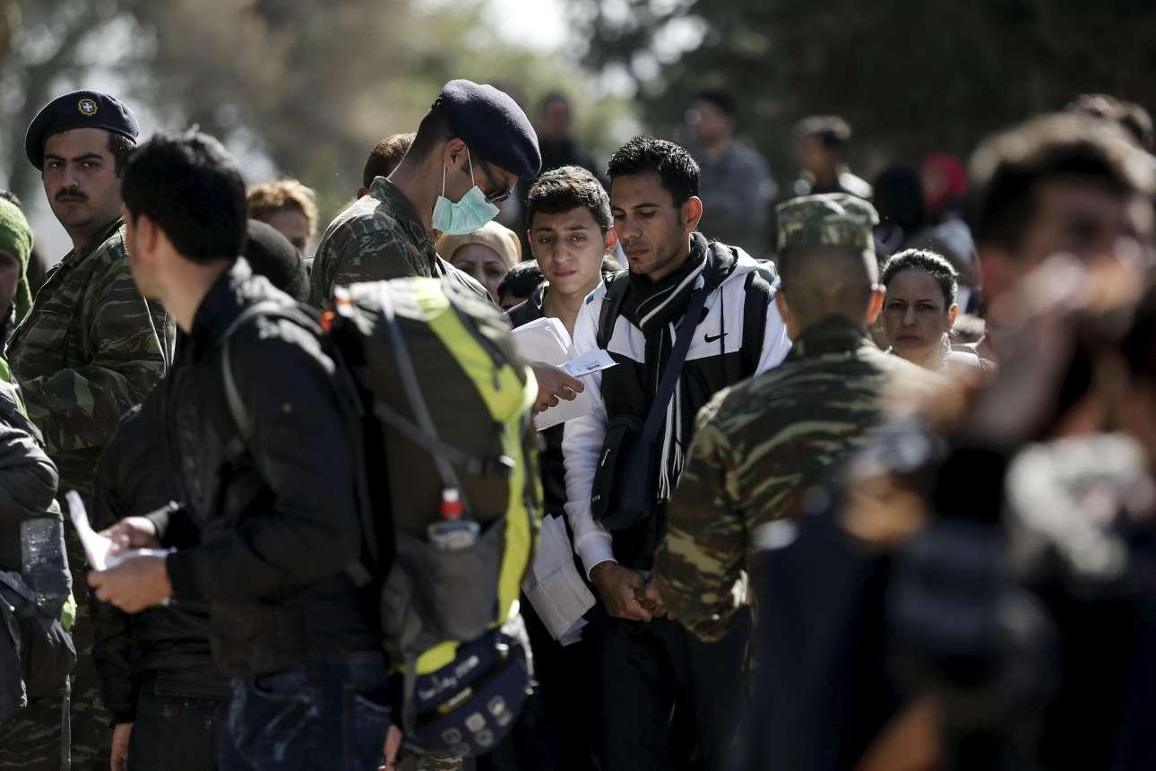 Ανδρες των Ενόπλων Δυνάμεων ελέγχουν τα χαρτιά προσφύγων προκειμένου να τους επιτρέψουν να εξέλθουν του hotspot για να συνεχίσουν το ταξίδι τους προς τα σύνορα με την ΠΓΔΜ