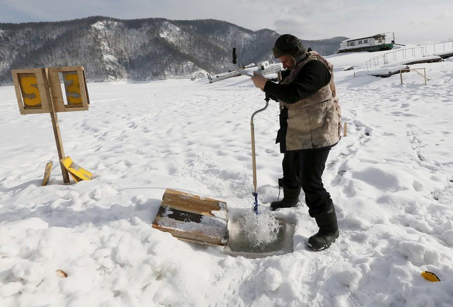 2 Μαρτίου/ Εργαζόμενος σε σταθμό πλοίων ανοίγει τρύπα στην παγωμένη επιφάνεια του ποταμού Γιενισέι στην Σιβηρία. Ετσι συλλέγεται το πόσιμο νερό