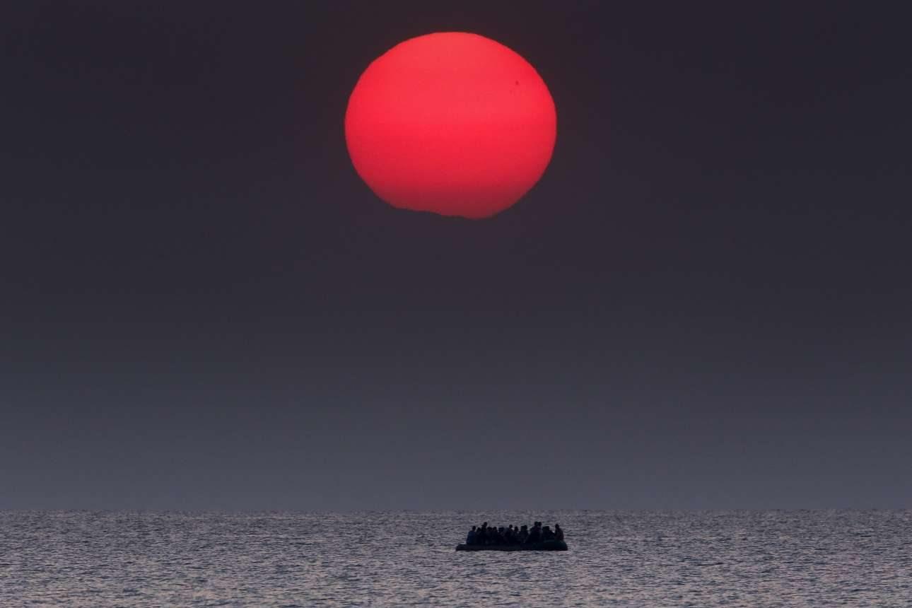 11 Αυγούστου, 2015. Στα ανοιχτά της Κω. Ο ήλιος δύει στο Αιγαίο. Μια βάρκα με πρόσφυγες πλέει στα ήρεμα νερά.