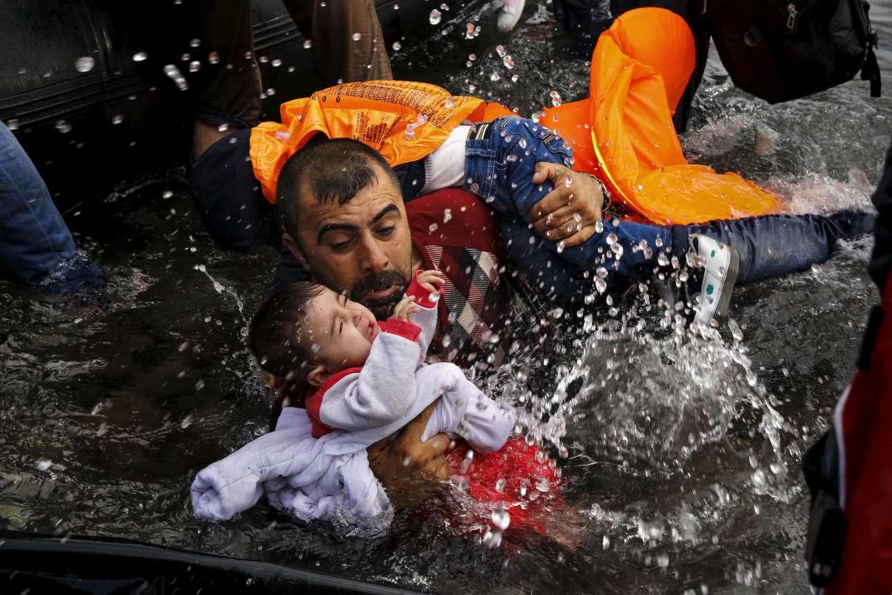 24 Σεπτεμβρίου 2015. Ενας σύρος πρόσφυγας κρατάει τα δύο παιδιά του προσπαθώντας να βγει στη στεριά στη Λέσβο.
