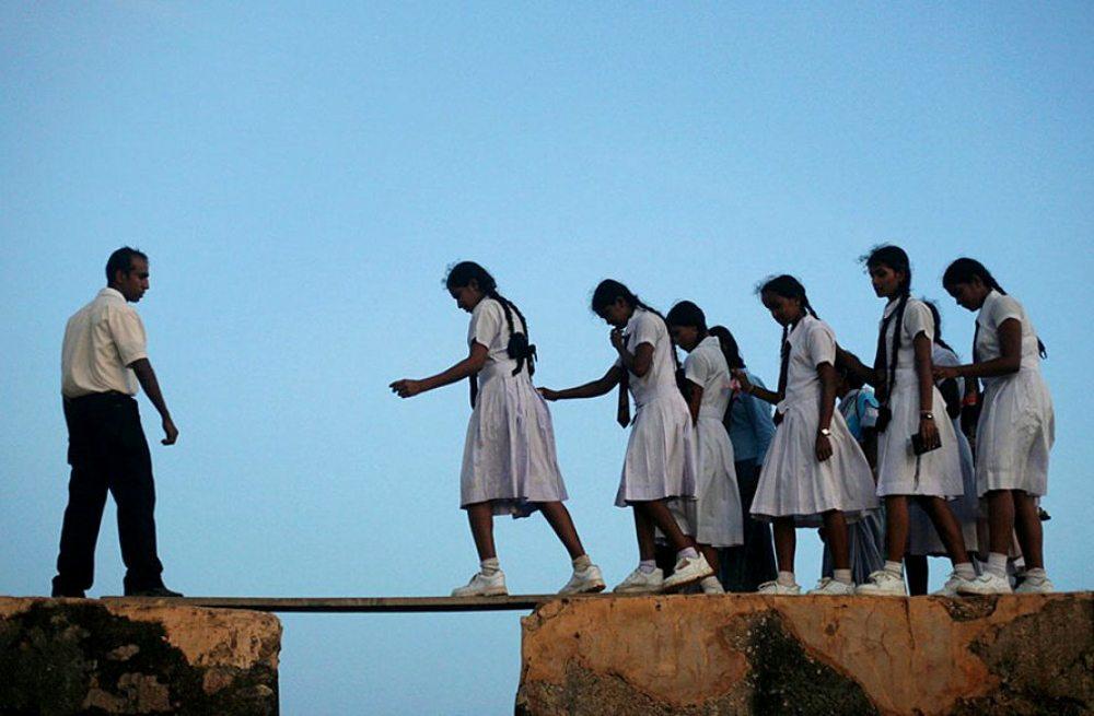 Σρι Λάνκα. Μια ομάδα μαθητριών χρησιμοποιεί μια σανίδα για να διασχίσει τα τείχη του Φόντε ντι Γκάλε, το οποίο κατασκεύασαν οι Πορτογάλοι στη χώρα τον 14ο αιώνα