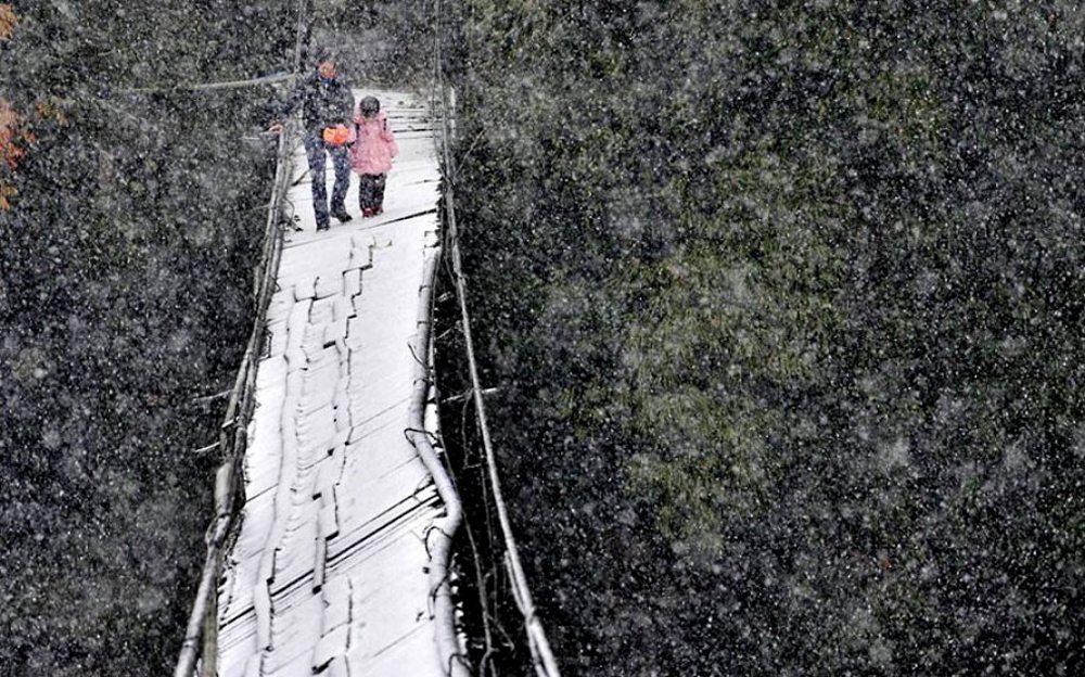 Σιχουάν, Κίνα. Διασχίζοντας μια εναέρια γέφυρα κι ενώ μαίνεται η καταιγίδα