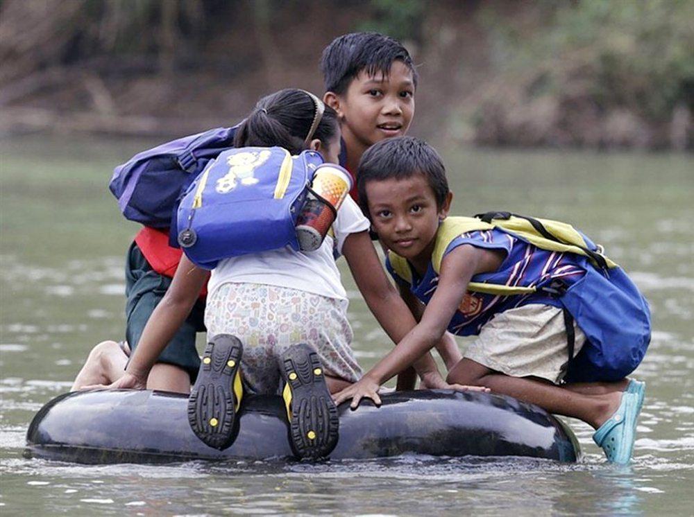 Ριτσάλ, Φιλιππίνες. Τα παιδιά χρησιμοποιούν μια σαμπρέλα για να διασχίσουν το ποτάμι