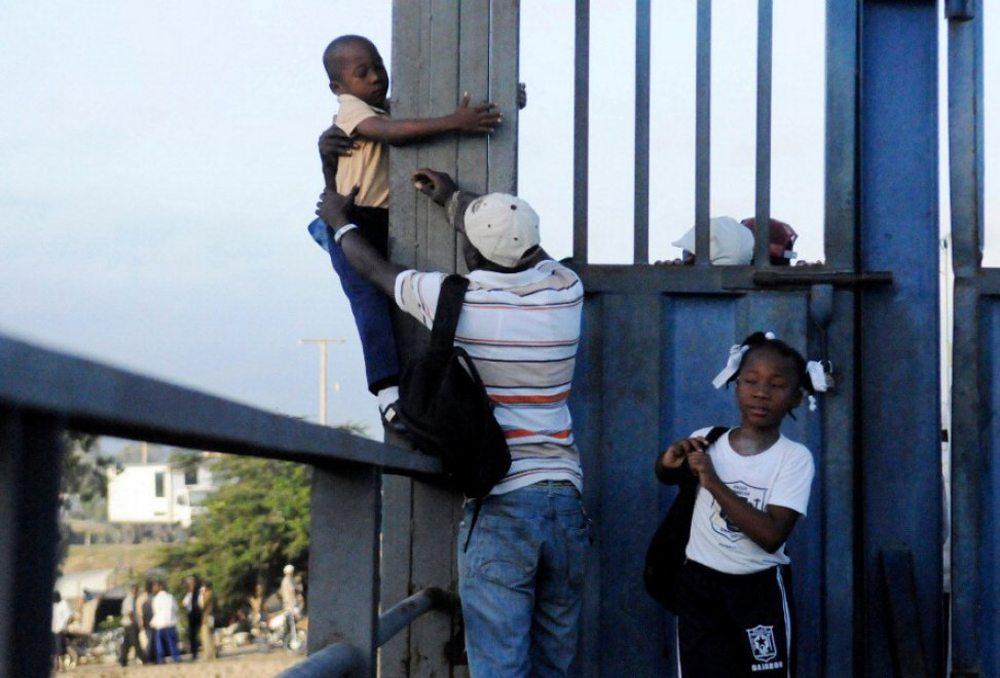 Νταγιαμπόν, Δομινικανή Δημοκρατία. Ενας πατέρας συνοδεύει τον γιο του στο σχολείο βοηθώντας τον να περάσει τα κάγκελα που χωρίζουν τη χώρα από την Αϊτή