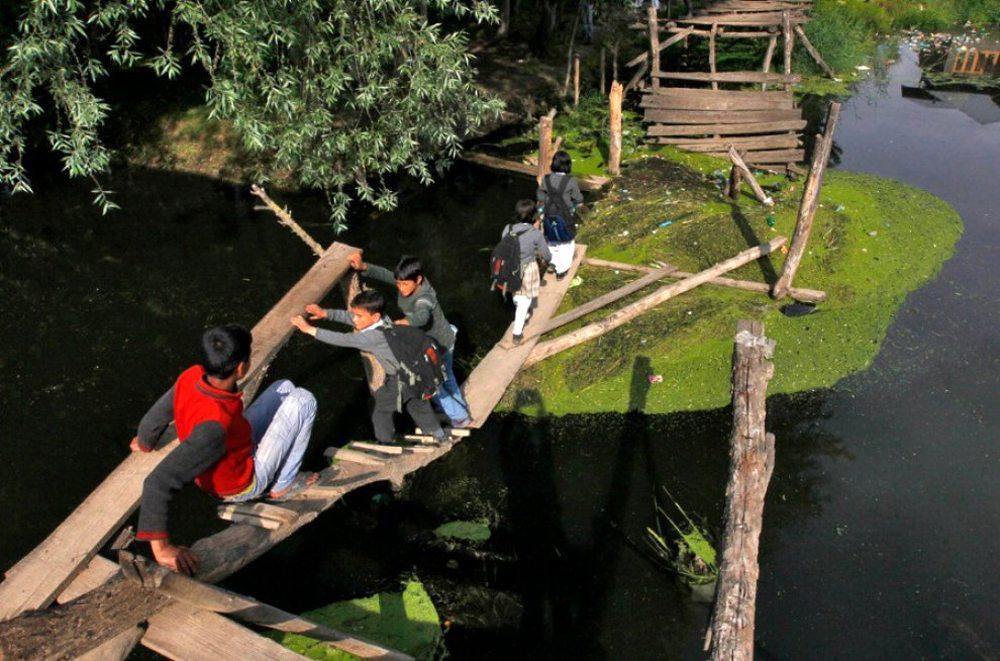 Σριναγκάρ, Κασμίρ. Κάποιοι μαθητές σκαρφαλώνουν αυτό που έχει απομείνει από μια γέφυρα. Μια πρόκληση με την οποία έρχονται καθημερινά αντιμέτωποι για να καθίσουν στα θρανία του σχολείου τους