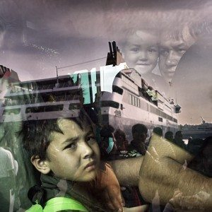 ATHENS, GREECE - OCTOBER 19:A migrant boy is seen through a bus window as refugees and migrants arrive aboard the passenger ferry Blue Star Patmos from the island of Lesbos at the port of Piraeus, near Athens, Greece, October 19, 2015(Photo by Milos Bicanski/Getty Images) *** Local Caption ***