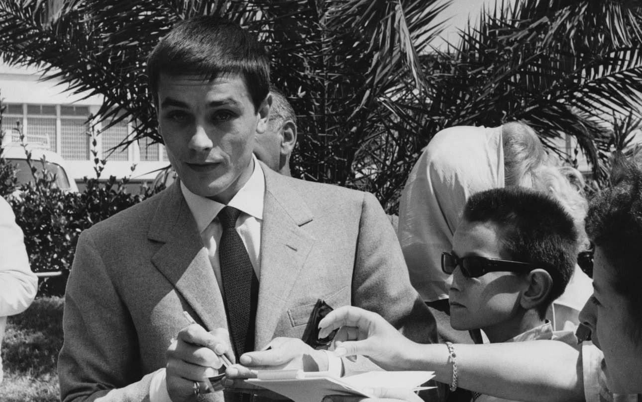 O Αλέν Ντελόν υπογράφει αυτόγραφα σε νεαρούς - και όχι μόνο - θαυμαστές του. Ηταν οι πρώτες του Κάννες. Είχε πάει για την κωμωδία του Ρενέ Κλεμέν «Quelle joie de vivre», που προβλήθηκε στην Ελλάδα με τον τίτλο «Γλυκιά που 'ν' η ζωή»