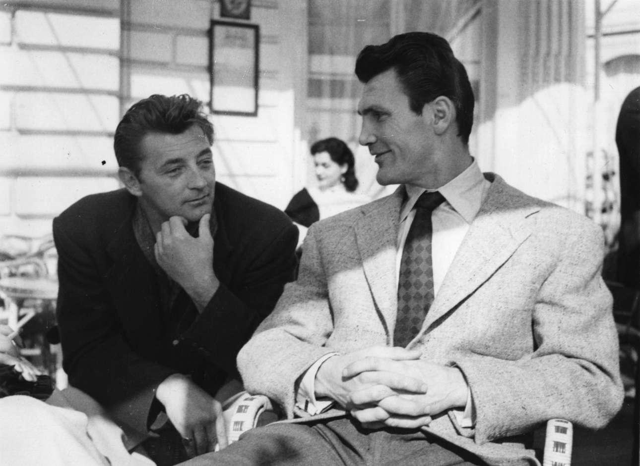 Μάιος 1954, δύο σκληροί του Χόλιγουντ, ο υπέροχος Ρόμπερτ Μίτσαμ (αριστερά) και ο απλά σκληρός Τζακ Πάλανς απολαμβάνουν λίγη σκιά και μια κουβέντα στο περιθώριο του 7ου Φεστιβάλ