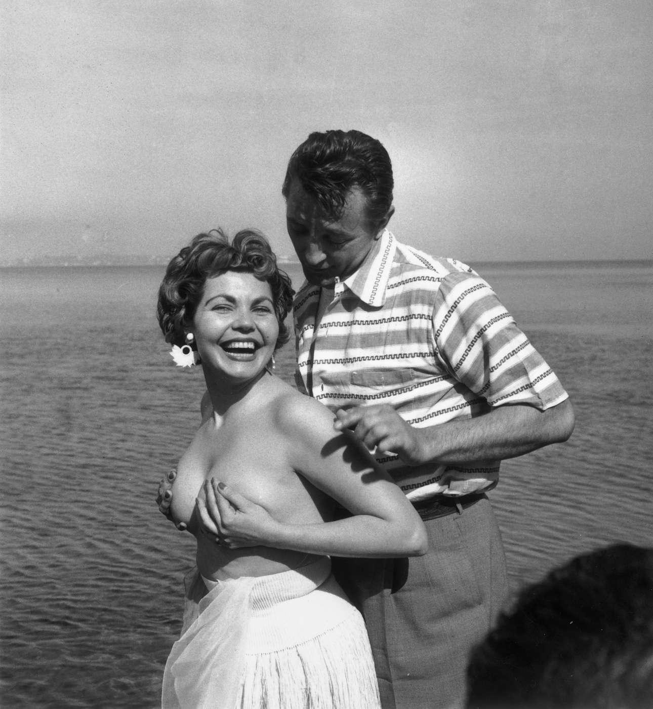 Απρίλιος 1954. Η φωτογραφία σκάνδαλο. Ο Ρόμπερτ Μίτσαμ αγκαλιάζει τη γυμνόστηθη βρετανή ηθοποιό Σιμόν Σίλβα. H ηθοποιός αποβλήθηκε από το φεστιβάλ. Ενας φωτογράφος έσπασε το χέρι του και ένας άλλος το πόδι του, σε μια προσπάθεια να βγάλουν τη φωτογραφία