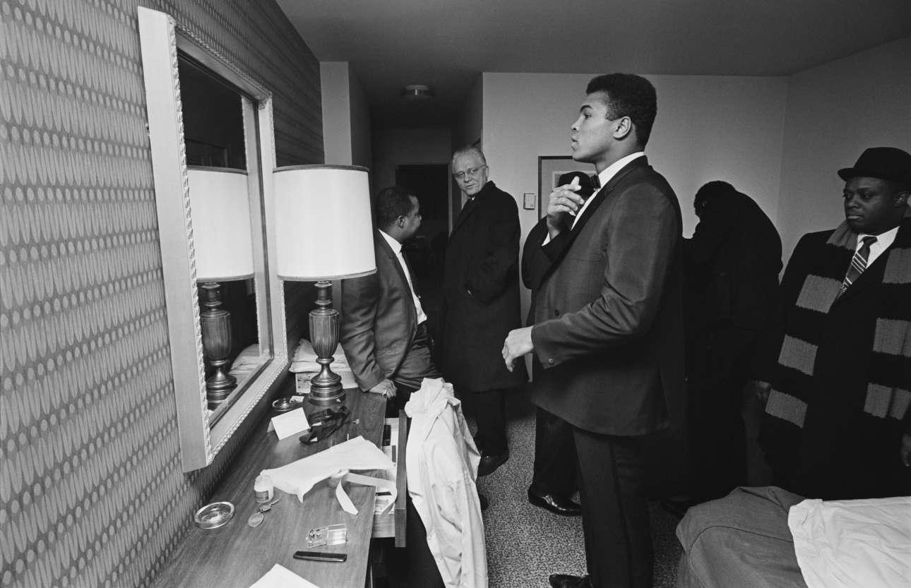 Φεβρουάριος 1967. Ο Μοχάμεντ Αλι στο δωμάτιο του ξενοδοχείου του με μέλη της συνοδείας του. Ελέγχει τις τελευταίες λεπτομέρειες για μια από τις πολλές δημόσιες εμφανίσεις του