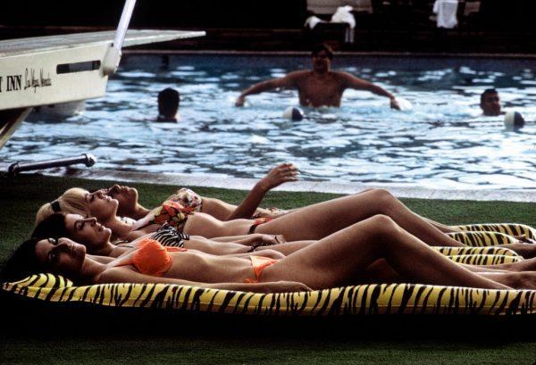 USA. Las Vegas, Nevada. Four sunbathers on leopard skin-printed rafts. 1968.