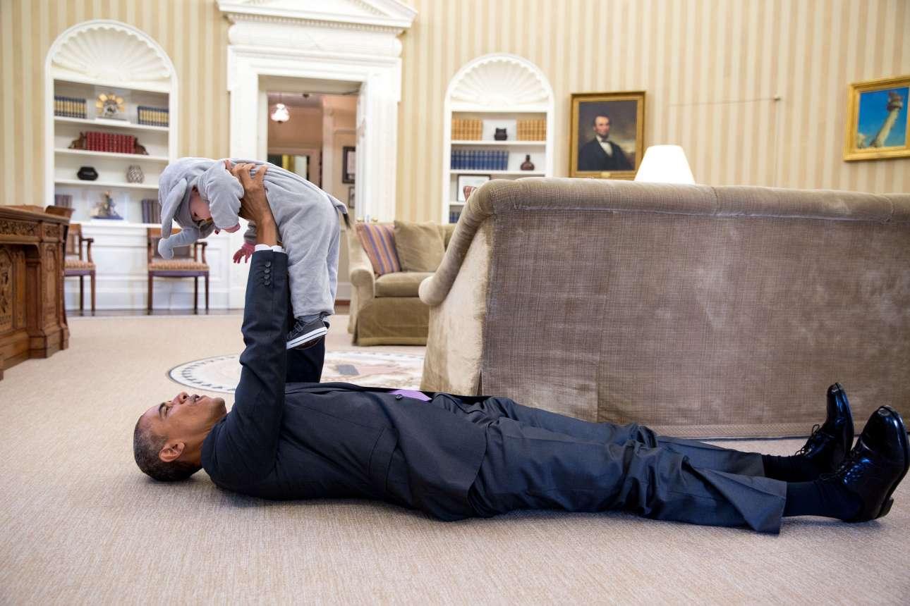 Ημερα του  Χάλοουιν και ο πρόεδρος Ομπάμα ξαπλωμένος σηκώνει ένα μωράκι ντυμένο ελέφαντας