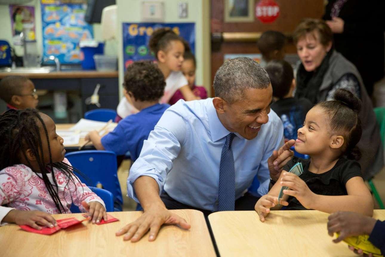 Ο Ομπάμα σε επίσκεψη του σε Κέντρο Φροντίδας Παιδιών τον Ιανουάριο του 2015.  Ο Πρόεδρος αντιδρά παιχνιδιάρικα σε κάτι που του είπε η μικρή Ακίρα Κούπερ