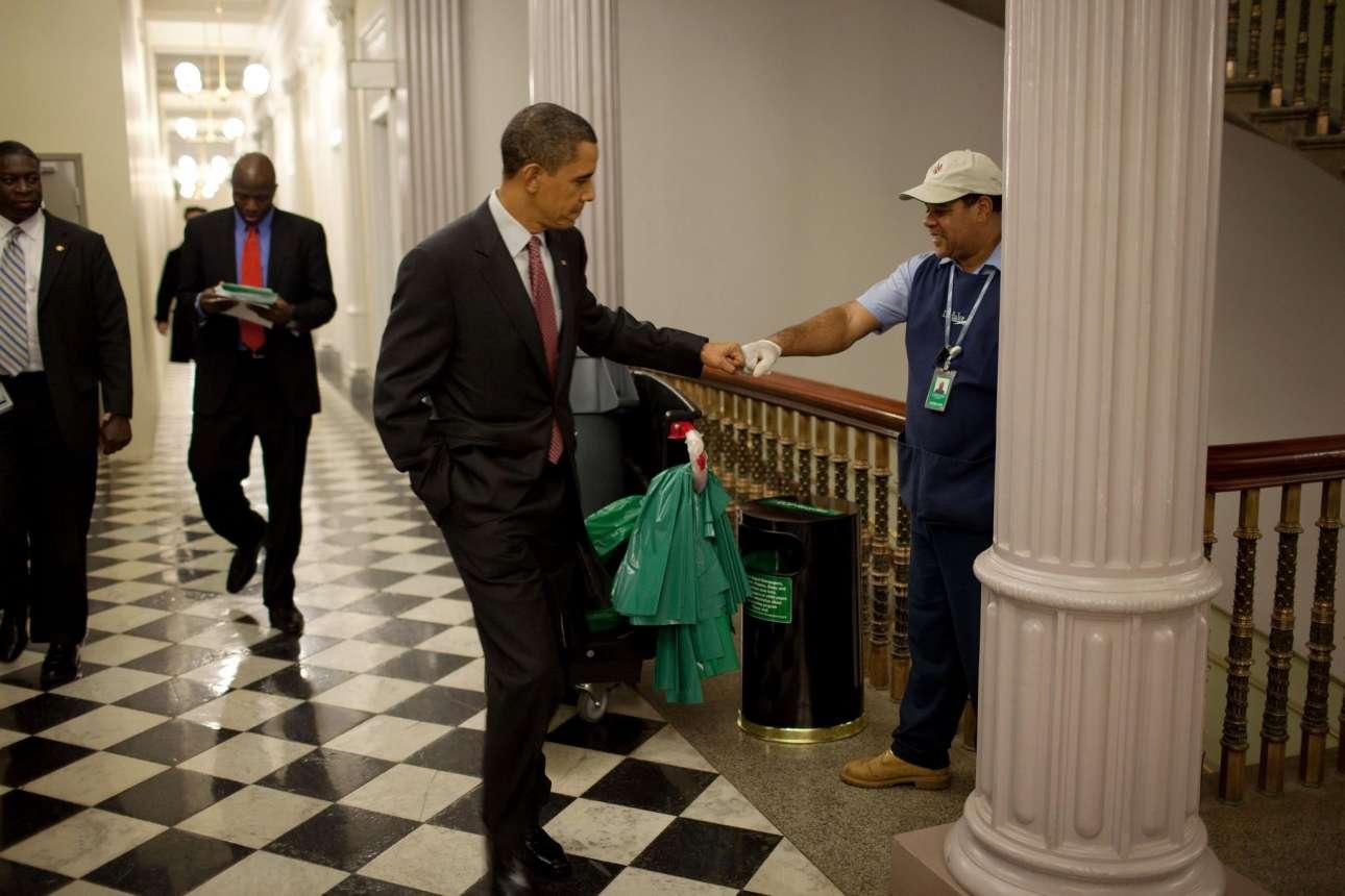 Από τις πρώτες φωτογραφίες του Ομπάμα που καθιέρωσε και την «κουλ» περσόνα του. Ο Ομπάμα χαιρετάει έναν επιστάτη στους διαδρόμους του Λευκού Οίκου με τη σήμα κατατεθέν χειρονομία του, τον χαιρετισμό - γροθιά