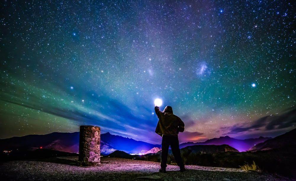 Ενα ουρανός γεμάτος αστέρια, παραμυθένια χρώματα και ένας άνδρας που φαίνεται σαν να κρατάει το φεγγάρι στο χέρι του