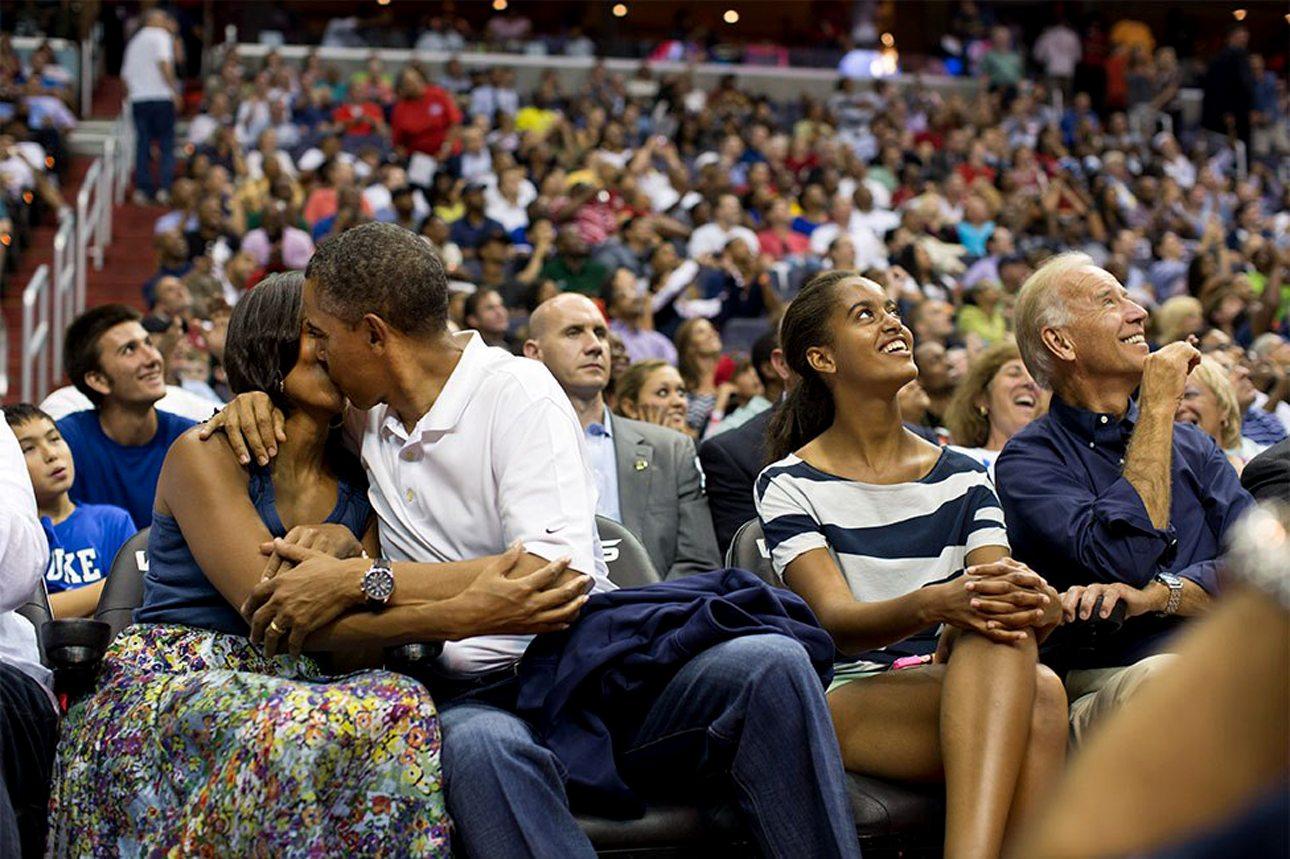 Ο Ομπάμα και η Μισέλ φιλιούνται όταν τους εντοπίζει η περίφημη «κάμερα φιλιού» (Kiss cam) σε αγώνα μπάσκετ στην Ουάσινγκτον. Δίπλα η κόρη του Ομπάμα και ο Αντιπρόεδρος γελάνε με το περιστατικό