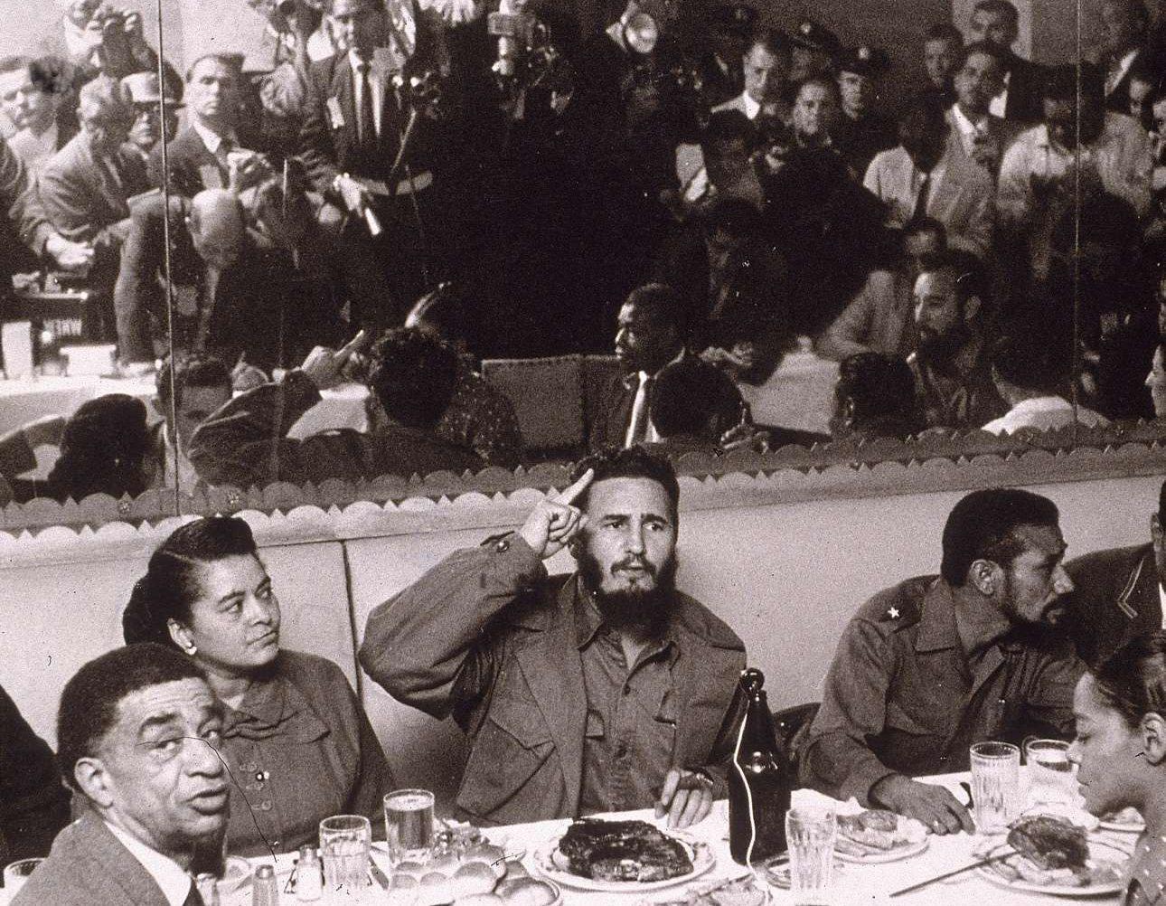 Γεμάτος αυτοπεποίθηση, ο νεαρός επαναστάτης μιλάει σε δημοσιογράφους κατά τη διάρκεια δείπνου στο Χάρλεμ της Νέας Υόρκης το 1959. Οι φωτορεπόρτερ και οι δημοσιογράφοι διακρίνονται στον καθρέφτη πίσω του