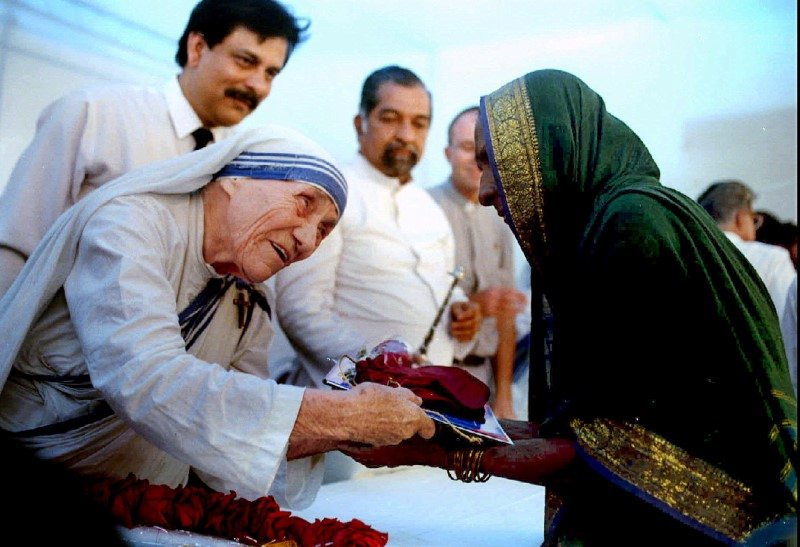 Mother Teresa presents documents for a new house to a villager from Latur in Bombay September 26, 1994. REUTERS/Savita Kirloskar/File Photo