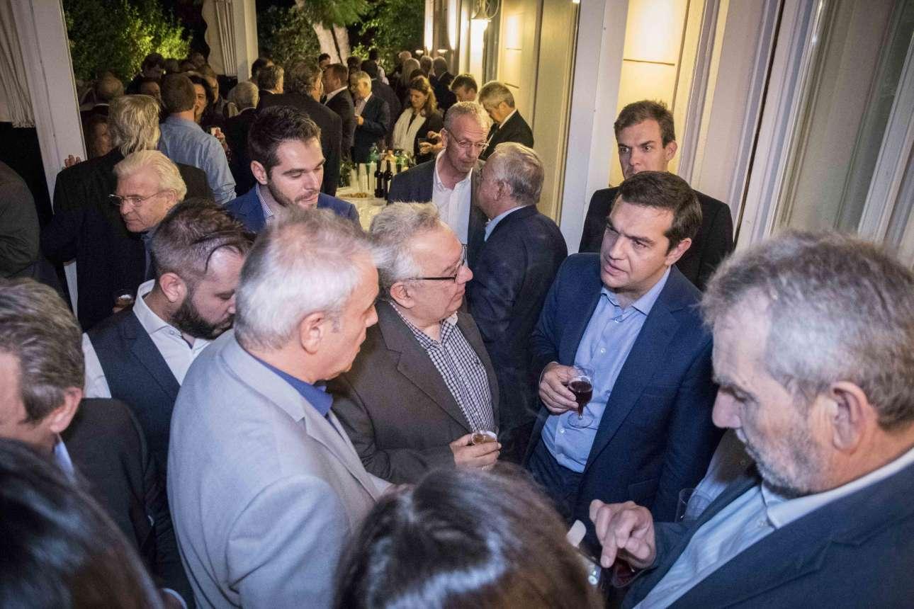 Ο Αλέξης Τσίπρας κρατά ένα ποτήρι κρασί και ακούει τους βουλευτές του
