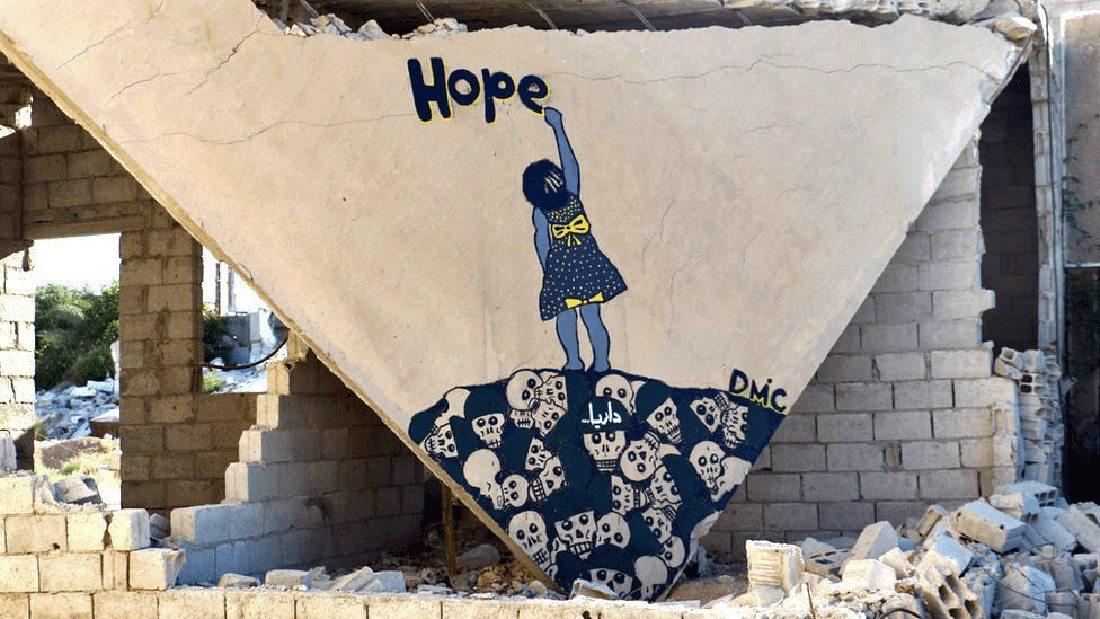 Ενα κορίτσι στέκεται πάνω στον σωρό από κρανία και γράφει τη λέξη Ελπίδα.  Μια εικόνα που έρχεται σε έντονη αντίθεση με το βομβαρδισμένο τοπίο. Αυτό ήταν το γκραφίτι που έκανε τα διεθνή μέσα να προσέξουν τον νεαρό καλλιτέχνη και να τον ονομάσουν «ο Μπάνκσι της Συρίας»
