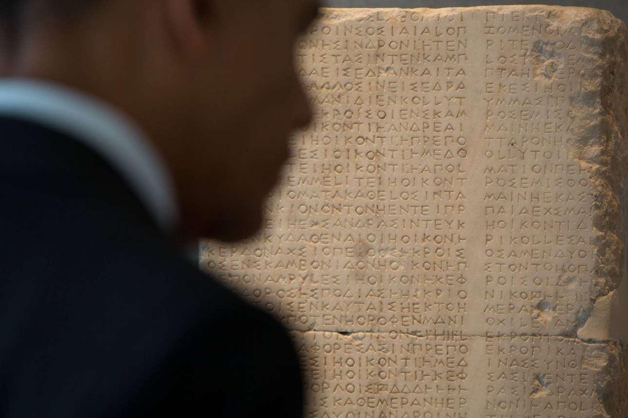 Η φιγούρα του Μπααράκ Ομπάμα σχηματίζεται σε πρώτο πλάνο ενώ ο φακός εστιάζει στην αρχαία επιγραφή