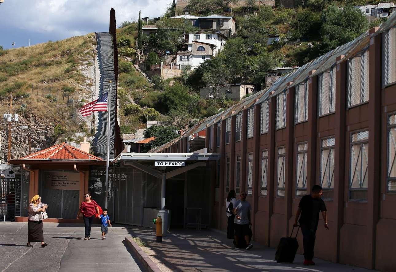 Ανθρωποι με βαλίτσες στα χέρια περπατούν στον σταθμό των συνόρων. Μία πινακίδα αναγράφει «Προς Μεξικό»