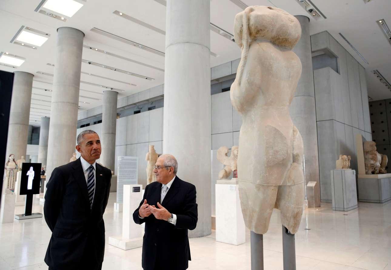 O Μπαράκ Ομπάμα με έναν μορφασμό μπροστά σε ένα έκθεμα του Μουσείου. Ο Δημήτρης Παντερμαλής εξηγεί