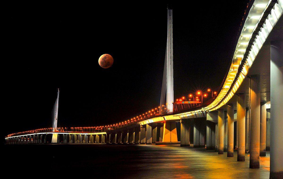 Τιμητική διάκριση, Κατηγορία Πόλεις: Ενα εντυπωσιακό κόκκινο φεγγάρι δεσπόζει πάνω από τη γέφυρα της πόλης Σεντζέν στην Κίνα
