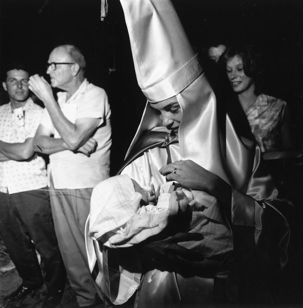 24th May 1965: A woman wearing the robes and hood of the American white supremecist organisation the Ku Klux Klan holding her baby at a klan meeting in Beaufort, South Carolina. (Photo by Harry Benson/Getty Images)