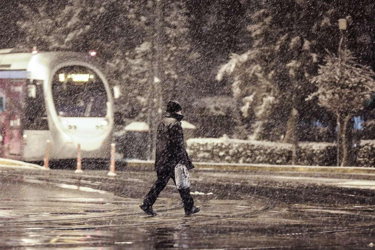 Πεζός διασχίζει τις γραμμές του τραμ στο Ζάππειο υπό πυκνή χιονόπτωση