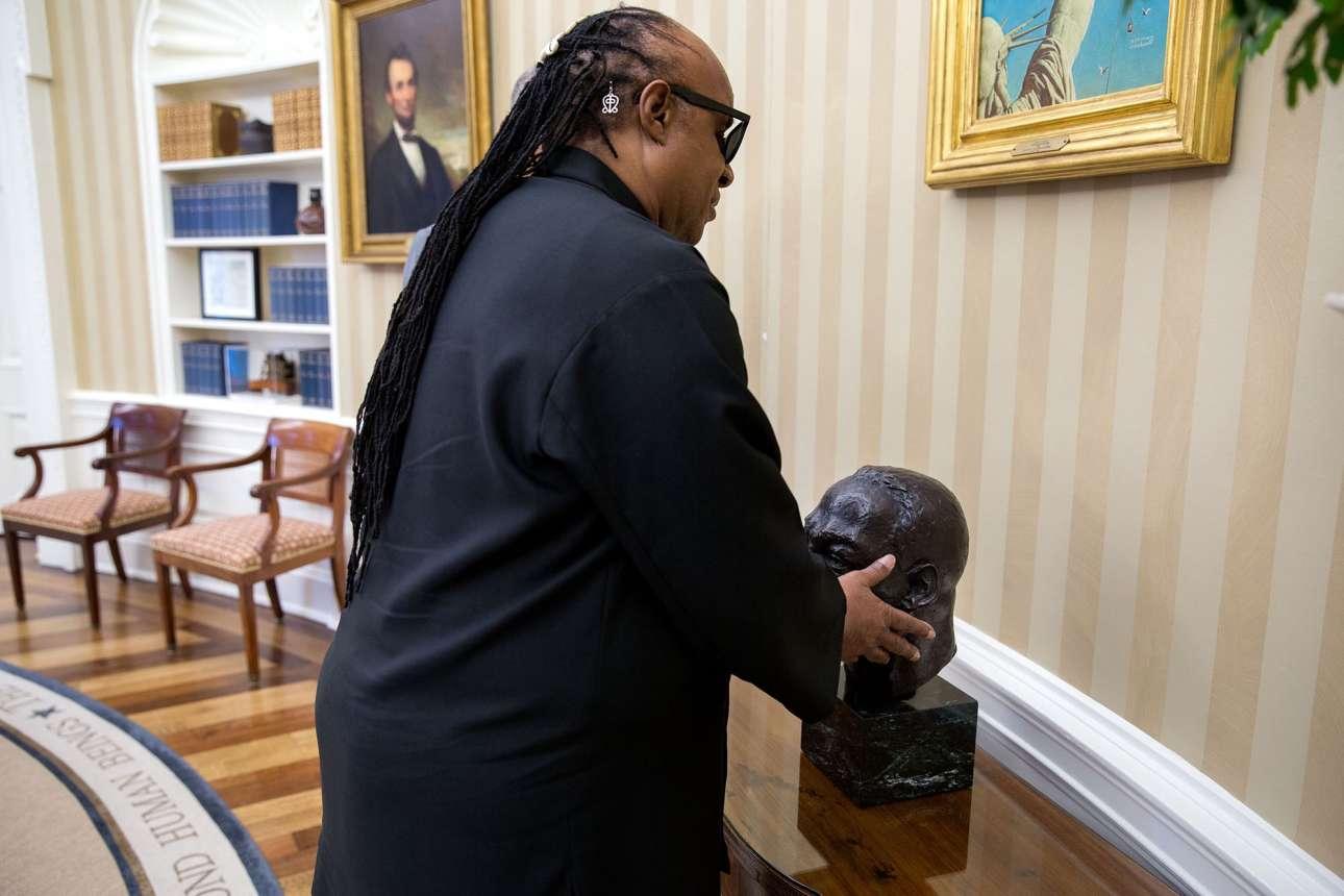 Αύγουστος: Ο Στίβι Γουόντερ αγγίζει την προτομή του Μάρτιν Λούθερ Κινγκ. Ο Ομπάμα του περιέγραφε όλα τα αντικείμενα στον χώρο, όταν ο διάσημος τραγουδιστής, που γεννήθηκε τυφλός, επισκέφθηκε το Οβάλ Γραφείο