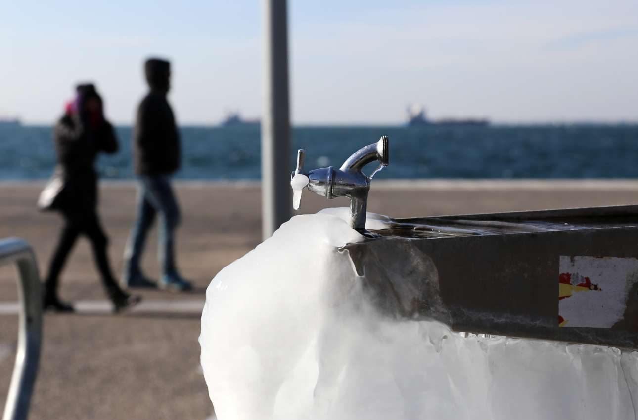 Ενα ζευγάρι περπατά στην παγωμένη Νέα Παραλία Θεσσαλονίκης
