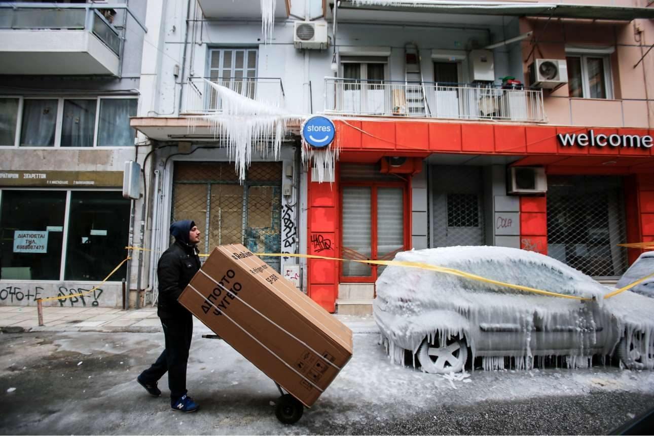 Στην παγωμένη Θεσσαλονίκη ένας άνδρας μεταφέρει ένα ψυγείο