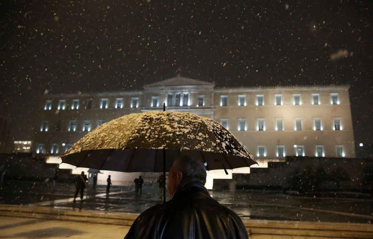Μια ομπρέλα προσφέρει προστασία στους περαστικούς μπροστά από το κτίριο της Βουλής