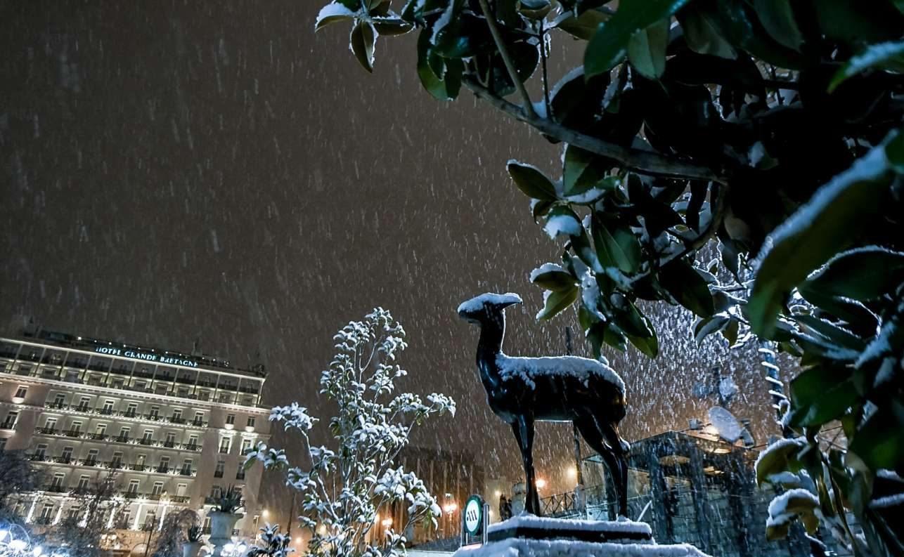 Το άγαλμα στην πλατεία Συντάγματος καλύπτεται από χιόνι, με φόντο το ξενοδοχείο «Μεγάλη Βρετάννια»