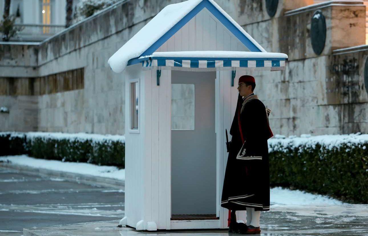 Φορώντας την υπέροχη χειμερινή κάπα ο εύζωνας φυλάει το χιονισμένο Μνημείο του Αγνωστου Στρατιώτη