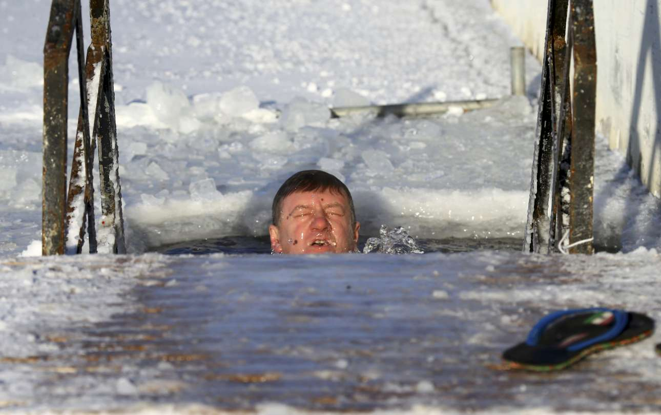 Ενας θαρραλέος άνδρας βουτάει στα παγωμένα νερά στο Μινσκ της Λευκορωσίας, με τη θερμοκρασία να αγγίζει τους -26 βαθμούς Κελσίου