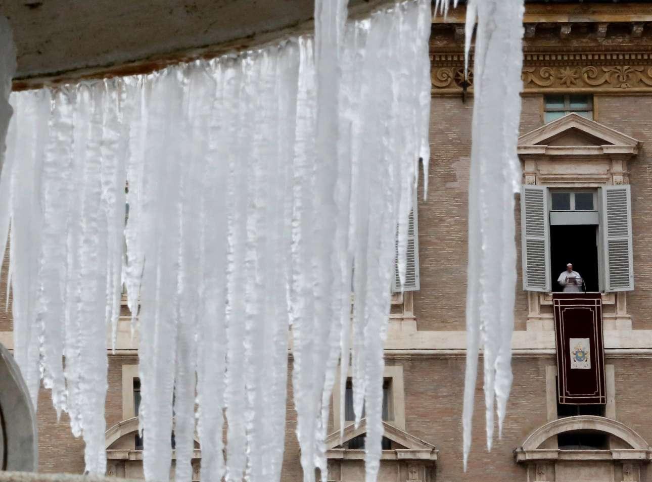 Το παγωμένο συντριβάνι της πλατείας του Αγίου Πέτρου στο Βατικανό με φόντο τον Πάπα Φραγκίσκο που τελεί την Κυριακάτικη λειτουργία
