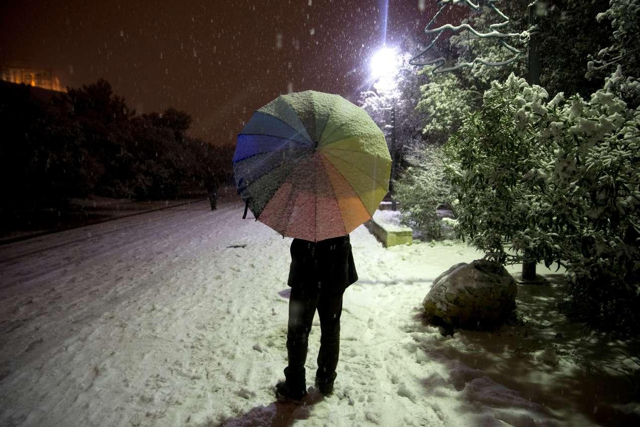 Θυμίζει σκηνικό από ταινία. Μια ομπρέλα, λιγοστοί πεζοί, χιονισμένος ο πεζόδρομος και στο βάθος η Ακρόπολη