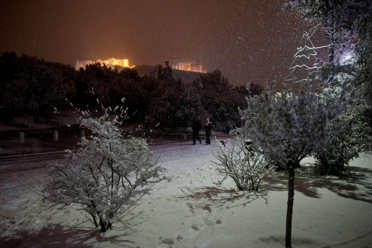 Το κίτρινο φως της Ακρόπολης και το λευκό του χιονιού στη Διονυσίου Αρεοπαγίτου συνθέτουν έναν ιδανικό σκηνικό για τους λιγοστούς τυχερούς διαβάτες.