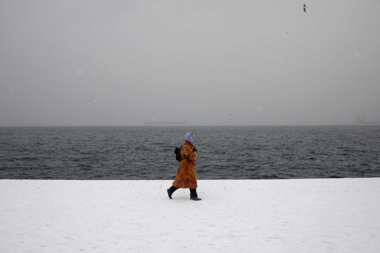 Μια εικόνα που θα μπορούσε να είχε βγει από ταινία του Αγγελόπουλου... μια γυναίκα κάνει βόλτα στην κάτασπρη παραλία της Θεσσαλονίκης