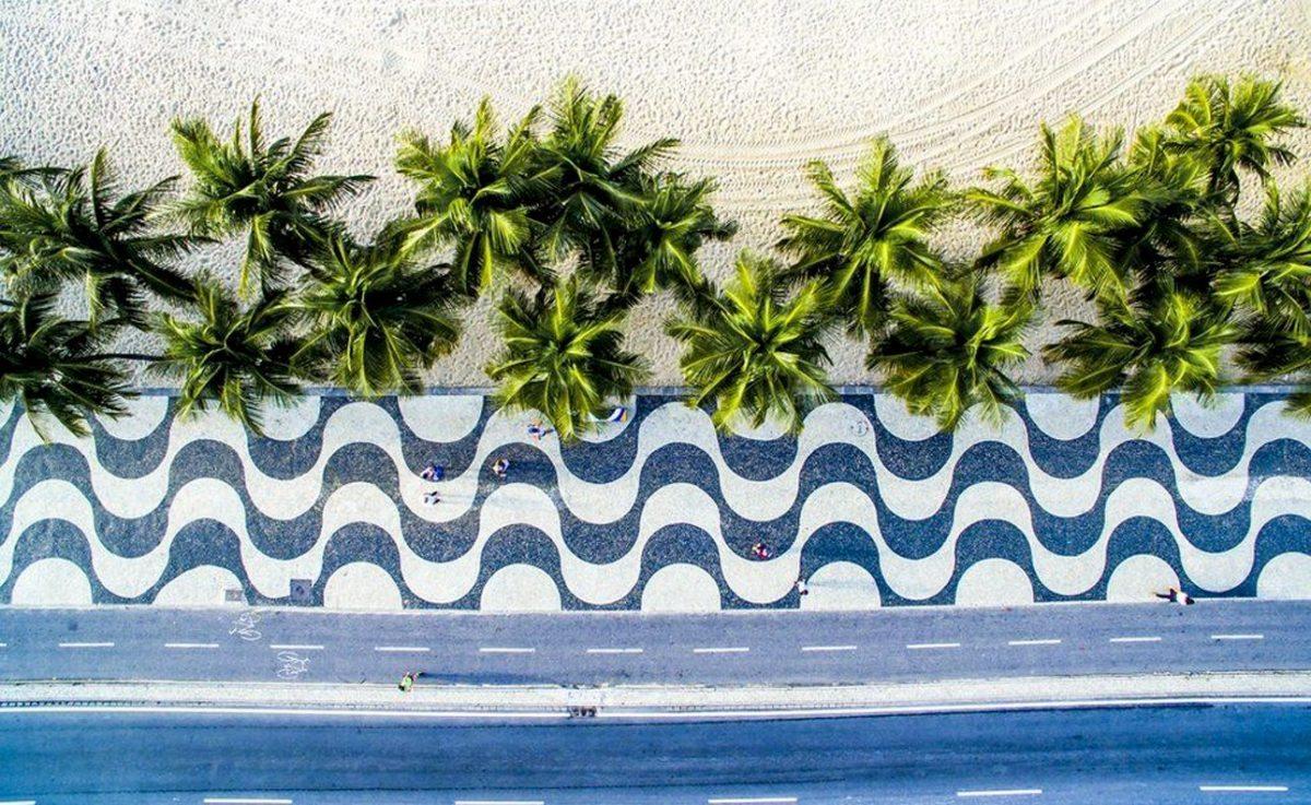 Πεζοί απολαμβάνουν τη βόλτα τους πάνω στο υπέροχο πλακόστρωτο με τα γραφιστικά σχέδια και υπό τη σκιά των φοινικόδεντρων, στην παραλία Κόπα Καμπάνα του Ρίο
