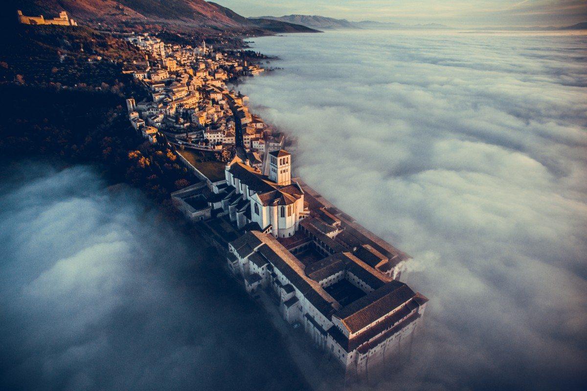 Η βασιλική του Αγίου Φραγκίσκου της Ασίζης στην Ιταλία,  λουσμένη στα χρώματα του δειλινού και στην ομίχλη. Ο φωτογράφος έστειλε το drone στον αέρα πάνω από τα σύννεφα από όπου «η θέα ήταν εκπληκτική»