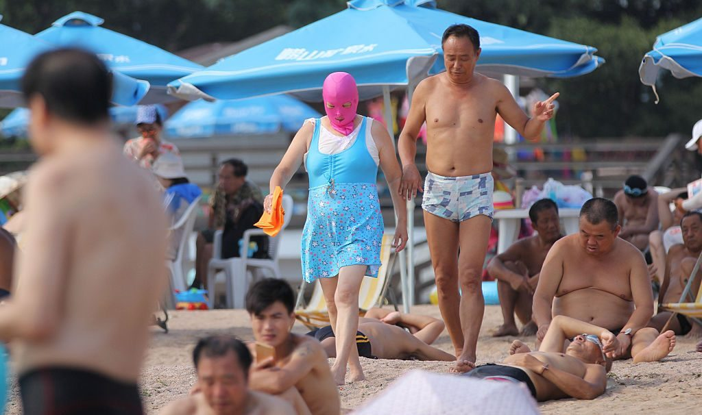 QINGDAO, CHINA - AUGUST 22: A woman wearing a facekini walks on beach on August 22, 2016 in Qingdao, Shandong Province of China. People wear facekinis to protect themselves from sun's rays, jellyfish and algae. (Photo by Huang Jiexian/VCG via Getty Images)