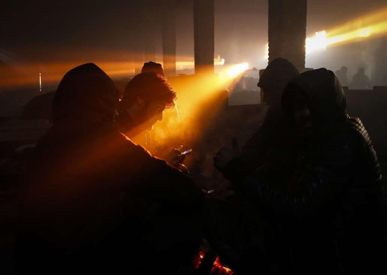 Στους -11 βαθμούς Κελσίου, μετανάστες προσπαθούν να ζεσταθούν δίπλα στη φωτιά, μέσα σε μια εγκαταλειμμένη αποθήκη στο Βελιγράδι