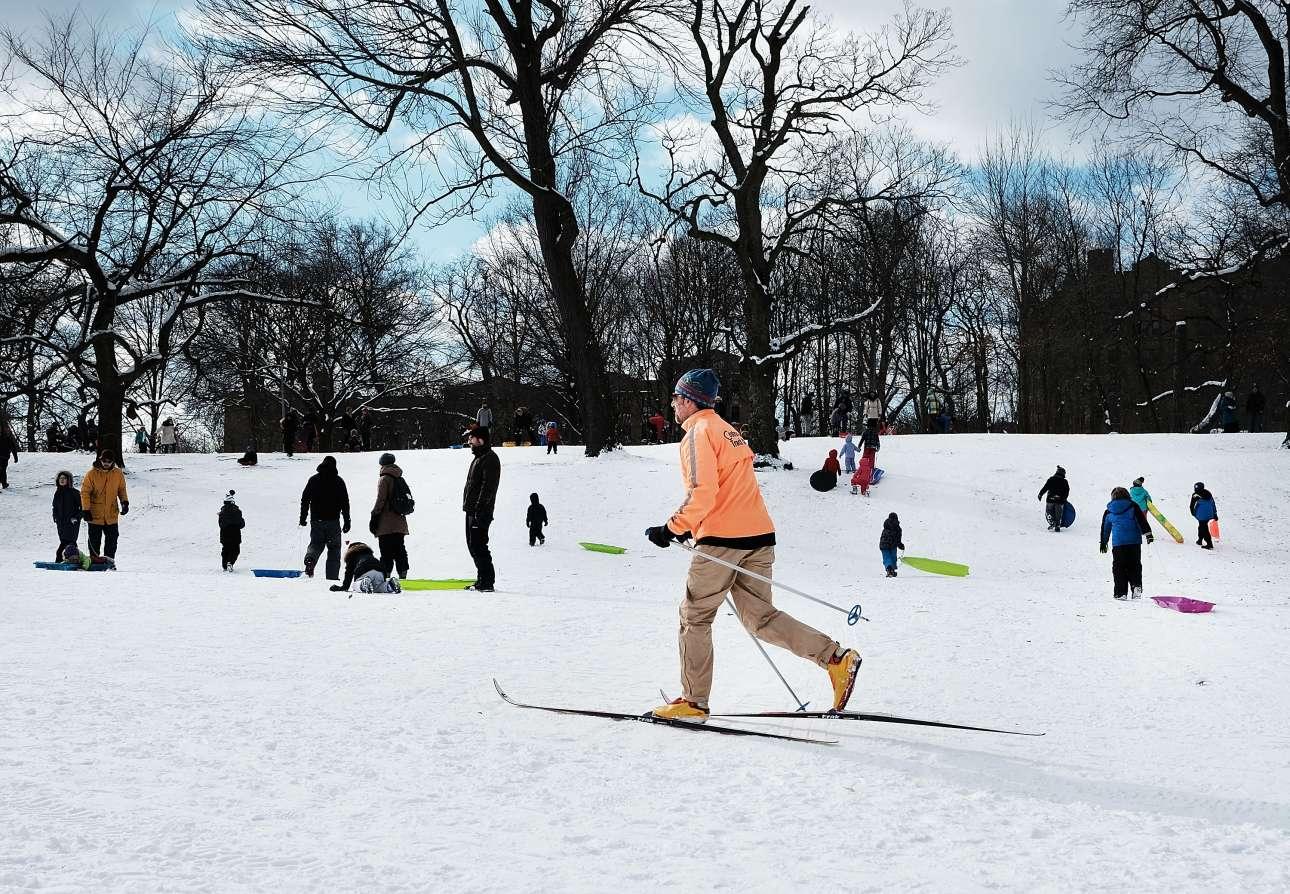 Ανθρωποι όλων των ηλικιών με σκι και έλκυθρα απολαμβάνουν το χιονισμένο πάρκο του Μπρούκλιν στη Νέα Υόρκη