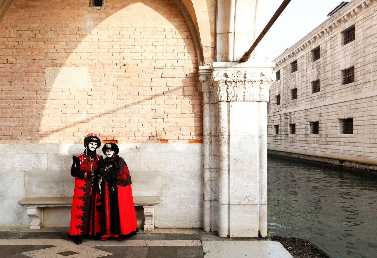 Ενα μασκαρεμένο ζευγάρι ποζάρει στην ιστορική πλατεία του Αγίου Μάρκου