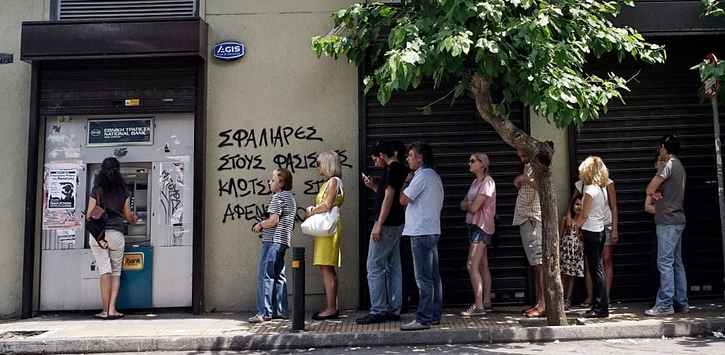 ATHENS, GREECE - JUNE 27: Greeks queue in front of the National Bank to use ATM to withdraw cash as Parliament holds an emergency session for the government's proposed referendum June 27, 2015 in Athens, Greece. Greece's fraught bailout talks with its creditors took a dramatic turn early Saturday, with the radical left government announcing a referendum in just over a week on the latest proposed deal . (Photo by Milos Bicanski/Getty Images)
