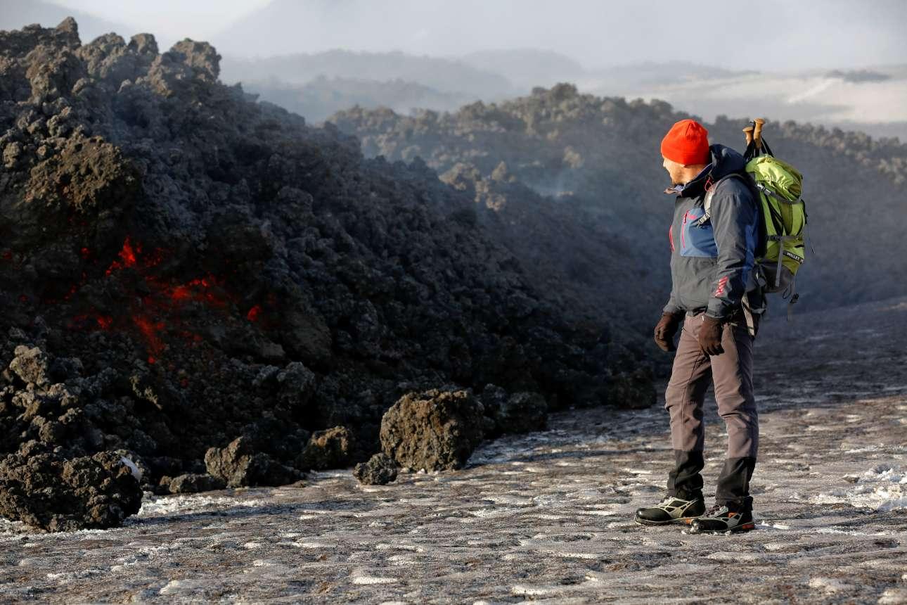 Ξεναγός του ηφαιστείου κοιτάζει τη λάβα που ρέει μετά την πρόσφατη έκρηξη της Αίτνας, στις 28 Φεβρουαρίου